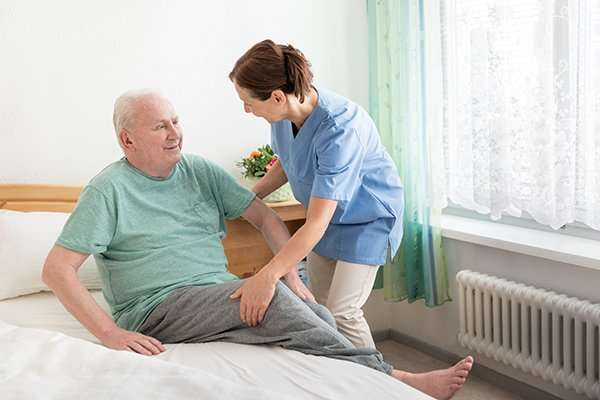 Home caregiver helping an elderly man out of bed