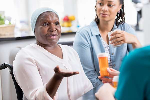 Aging patient discusses medication with nurse