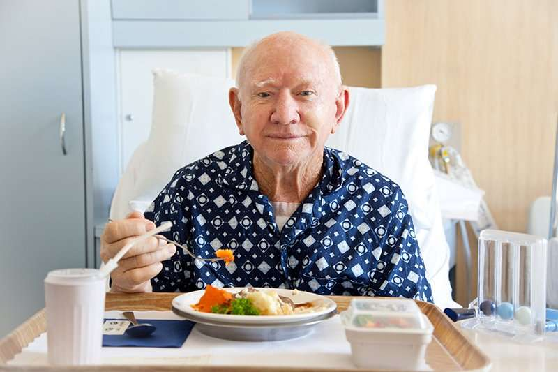 senior man eating in hospital room