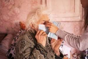 woman with grandmother assisting with mask