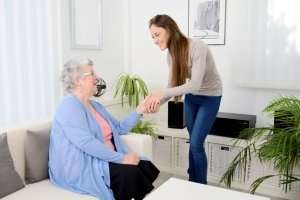 family caregiver holding hands with elderly loved one