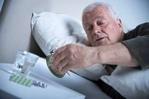 senior man waking up and looking at his alarm clock